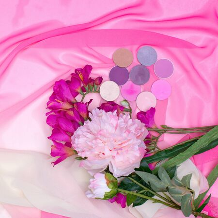 set of cosmetics: colorful eye shadow and peonies on a pink background. top view