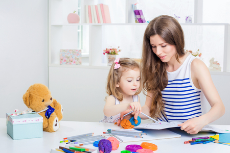 beautiful young mother and her little daughter drawing with crayons on the album. mother and daughter having fun at home. Standard-Bild