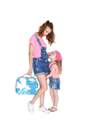 castors: beautiful young mother and lovely daughter is going on a trip. woman and child with a suitcase on castors on white background Stock Photo