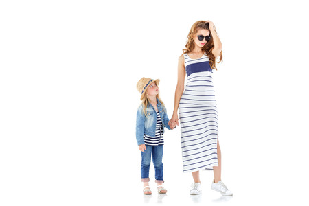 beautiful  mother walks, and little daughter pulls her in another direction. the child is naughty. isolated on white background Stock Photo