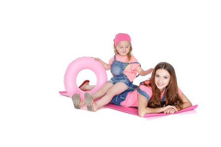 rubber ring: beautiful mom and lovely daughter with a pink rubber ring lying on a beach Mat