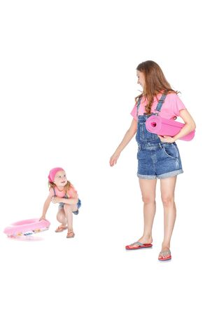 rubber ring: happy family going to the beach. beautiful mom and lovely daughter with a pink rubber ring and  beach Mat Stock Photo