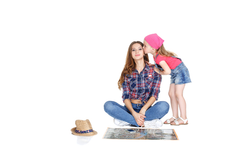intend: Happy woman and little girl  with map. daughter kissing mother. Isolated on white background. Stock Photo