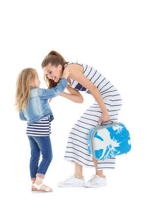 castors: daughter tickles mom. woman and child with a suitcase on castors on white background
