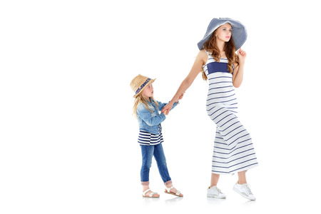 beautiful  mother with the hat walks, and little daughter pulls her in another direction. the child is naughty. isolated on white background Stock Photo