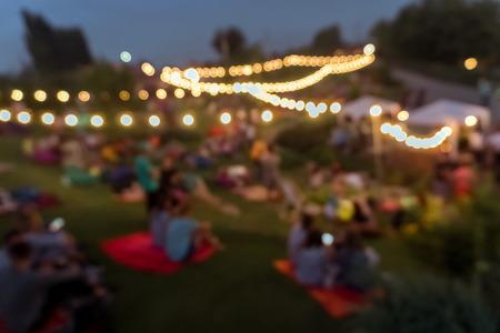 家族や友人と公園でピクニックする人をぼかし。夜フード フェスティバル