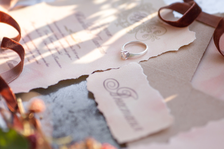 golden ring: wedding ring lies on the invitation. Golden ring with diamond Stock Photo
