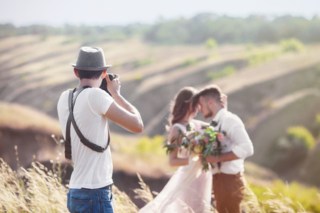 un fotógrafo de bodas toma fotos de la novia y el novio en la naturaleza, el fotógrafo en la acción Foto de archivo