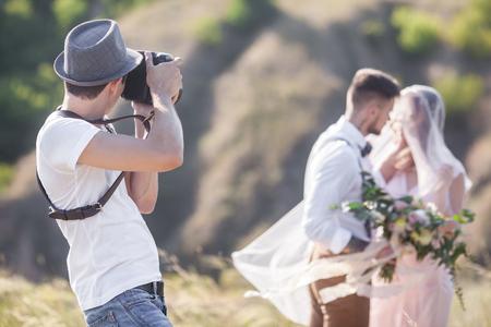 ein Hochzeitsfotograf nimmt Bilder von der Braut und Bräutigam in der Natur, der Fotograf in Aktion Lizenzfreie Bilder