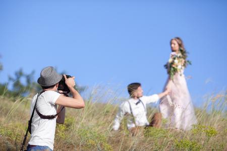 un fotógrafo de bodas toma fotos de la novia y el novio en la naturaleza, el fotógrafo en la acción