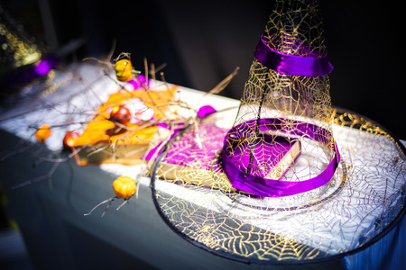 Halloween. witch hat with purple ribbon lying on the table