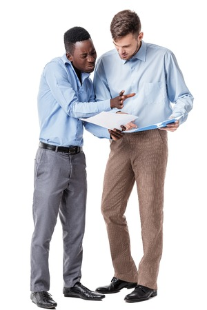African-American and Caucasian businessman discussing a contract and a quarrel on a white background. a disadvantage Stock Photo