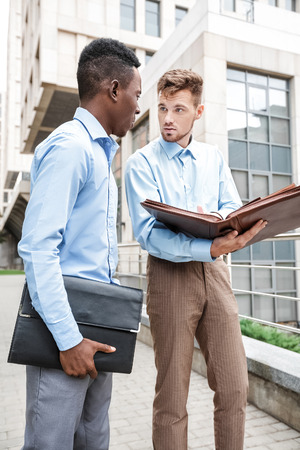 american banker: African American businessman and a Caucasian businessman discussing and looking at the documents on city background, bottom view