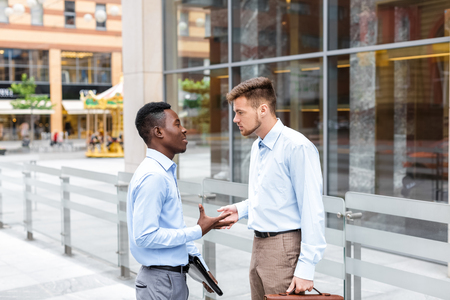 African American businessman and a Caucasian businessman discussing and looking at the documents on city background