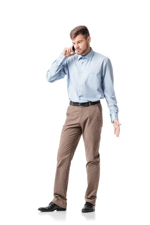 perturbed: Portrait of  indignant businessman talking on the phone isolated on a white background