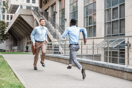 African American businessman and Caucasian businessman running to meet each other on  background of the city. clash of interests Stock Photo