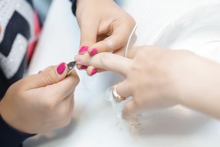 nailart: manicure specialist care by finger nail in beauty salon. Manicurist uses  professional manicure tool. Stock Photo