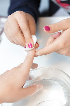 manicure specialist care by finger nail in beauty salon. Manicurist uses  professional manicure tool. Stock Photo