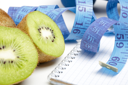 healthy eating, diet and weight loss, detox . dumbbells, kiwi and measuring tape Stock Photo