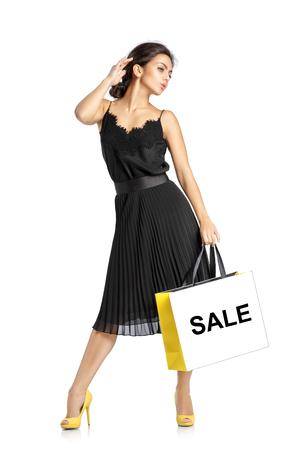 人、販売、ブラックフラ イデー、高級コンセプト - 白い背景で隔離の買い物袋と黒のドレスでセクシーな女性。
