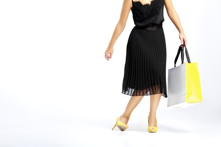 or spree: people, sale, black Friday and luxury concept - woman in black dress with shopping bags  on white background.
