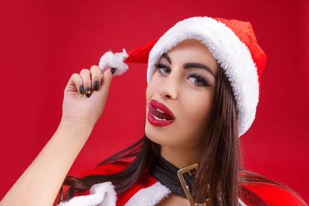 sexy woman in clothes of Santa Claus clown and fooling around on a red background. cartoon