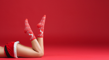 Mrs santa claus legs in Christmas stockings on red background