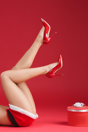 mrs  santa claus: Mrs santa claus legs in shoes with heels with christmas gift on red background