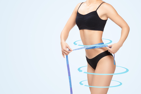Athletic  woman measuring her waist by blue measure tape after a diet