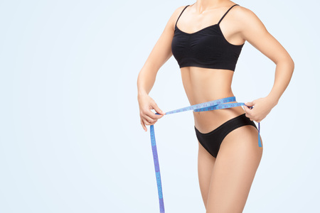 Athletic  woman measuring her waist by blue measure tape after a diet on a blue background