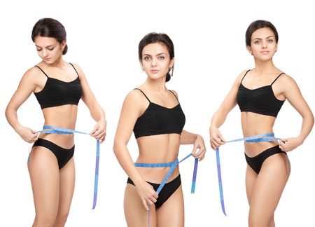 Athletic  woman measuring her waist by blue measure tape after a diet on a white background