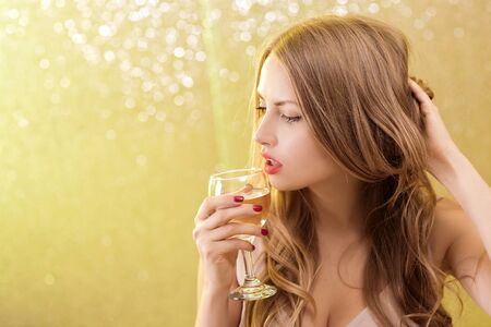 hollywood christmas: Fashion portrait of sexy blond woman with glass of champagne at party, drinking champagne over glowing background. Christmas and New year holiday