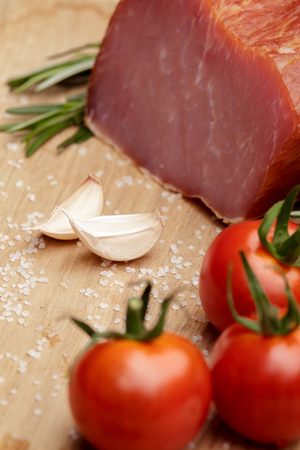 Piece of smoked Ham with some fresh mushrooms, tomato, garlic and herbs on wooden background. rustic style