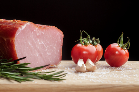 Piece of smoked Ham with some fresh mushrooms, tomato, garlic and herbs on wooden Board on black background