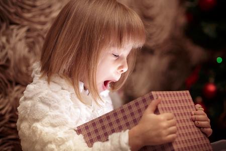 笑みを浮かべて少女はクリスマス ツリーの背景にマジック クリスマス ギフト ボックスを開きます
