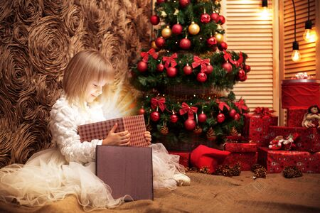 little smiling girl opens a magic Christmas gift box on the background of the Christmas tree