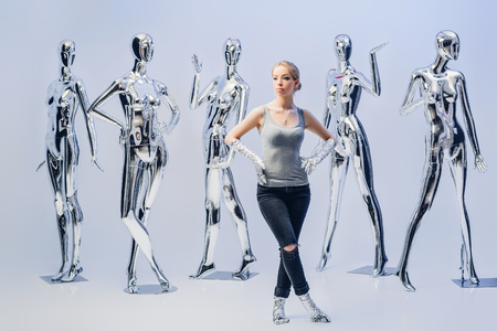attractive woman on background of many  metallic shiny mannequin Stock Photo
