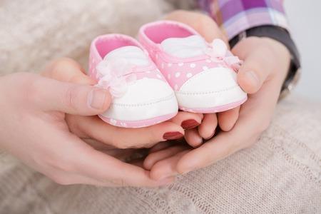 生まれたばかりの赤ちゃんのママとパパの手の中のピンクのブーツ。妊娠 写真素材