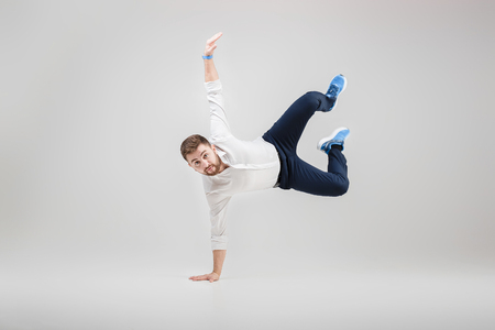 young happy businessman with beard in shirt break dancing on gre