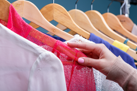 female hand selects colorful clothes on wood hangers on rack in