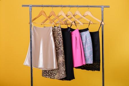 skirts: women colorful skirts on hangers on  rack on orange background.