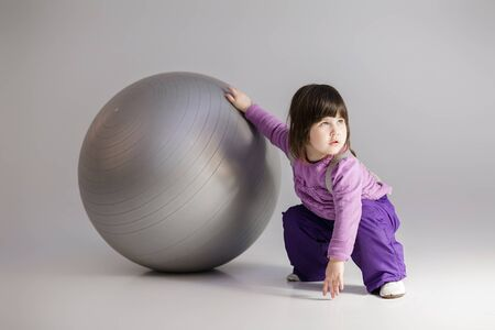 little girl in purple clothes with big ball for fitness on gray