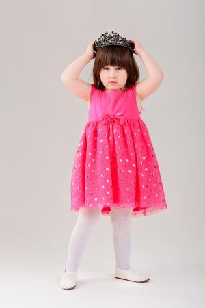灰色の王冠とピンクの姫の美しい小さな女の子ドレスします。 写真素材