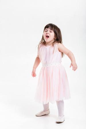 beautiful little girl in pink Princess dress naughty on a gray b