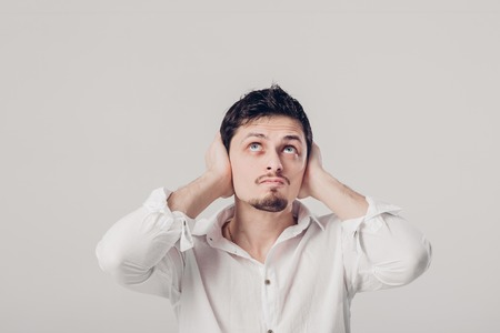 portrait of young man in shirt covers his ears with his hands ag Stock Photo