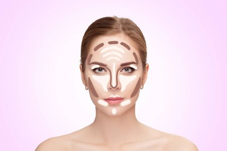 Contouring. Make up woman face on pink background.  Professional