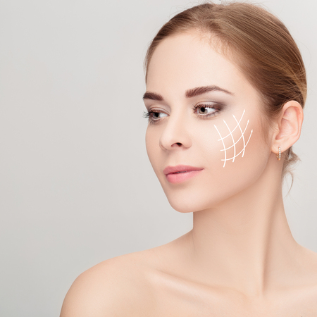 Spa portrait of woman with arrows on her face on grey background