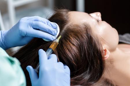 Naald mesotherapie. Cosmetische injecties in het hoofd van de vrouw. naar s