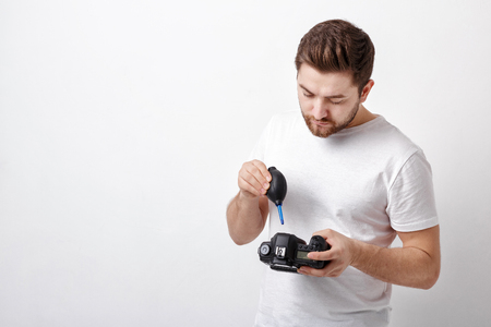 air cleaner: photographer cleaning camera with vacuum pump. hand blower dust