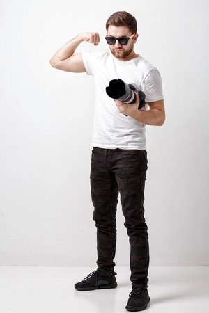 professional photographer in t-shirt use digital camera with lon